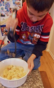 My grandson Georgie, furiously mashing the bananas with a potato masher.